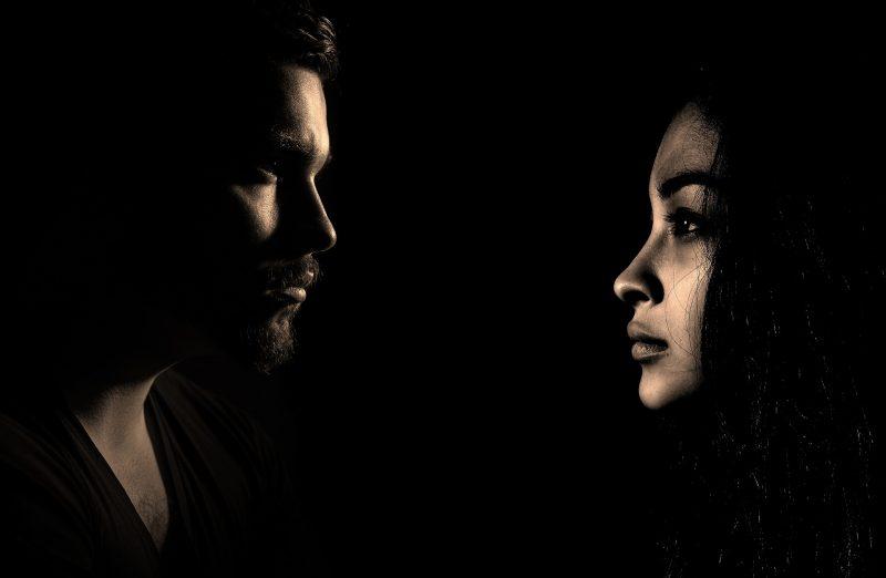 Hombre y mujer mirándose a la cara sobre fondo negro
