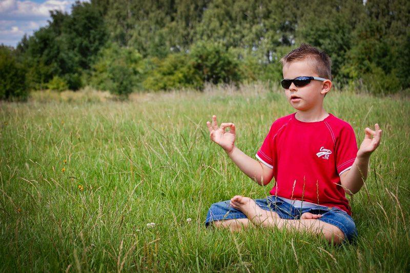 Niño meditando sobre hierba