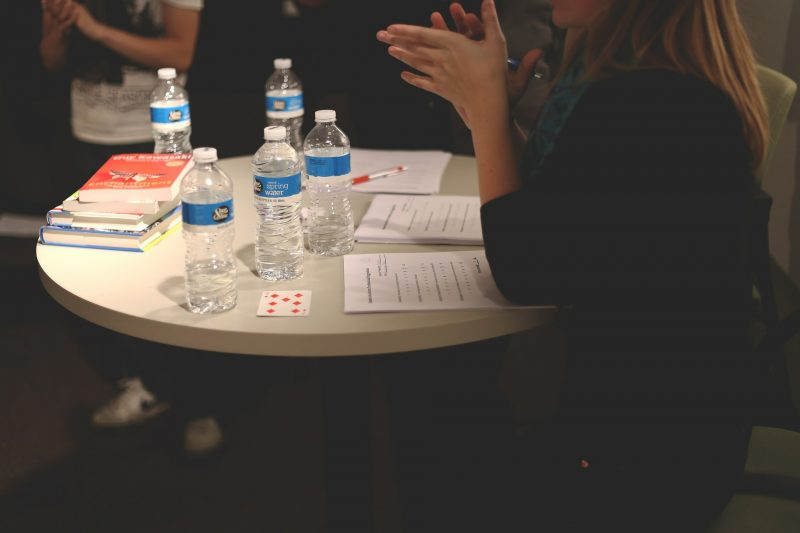 Mujer sentada en una mesa redonda con papeles, libros y botellas de agua