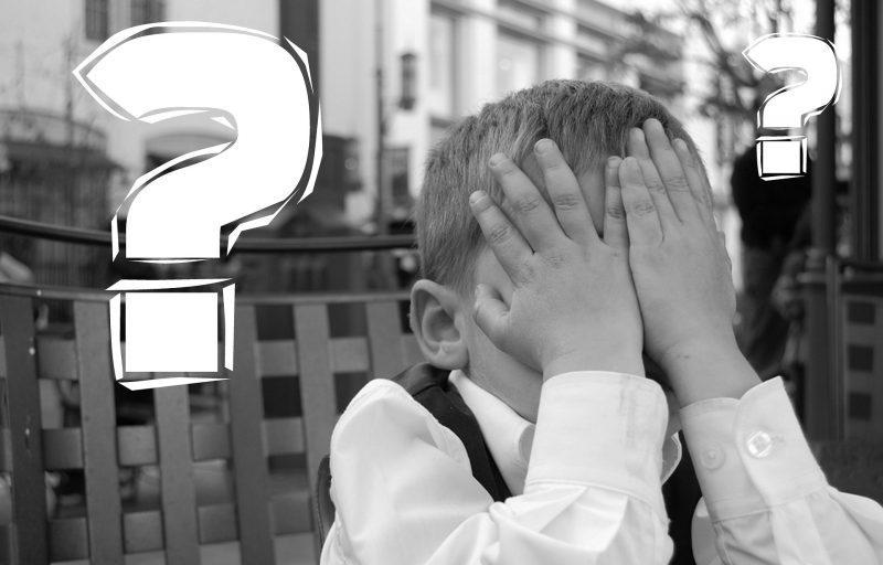 Niño se tapa la cara con las manos. Interrogaciones blancas superpuestas.