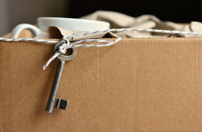 Llave atada a un cordel pendiendo de caja de cartón