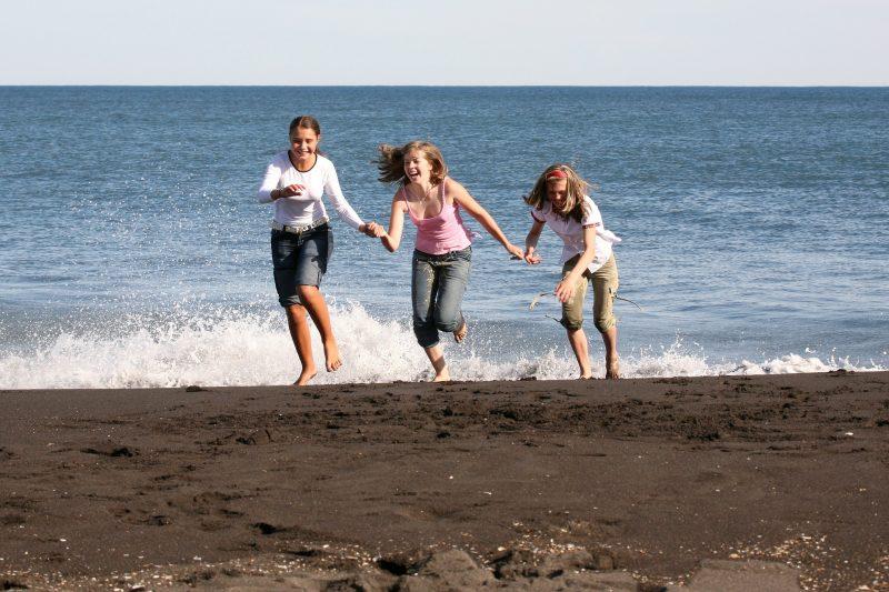 Adolescentes jugando y riendo en la playa