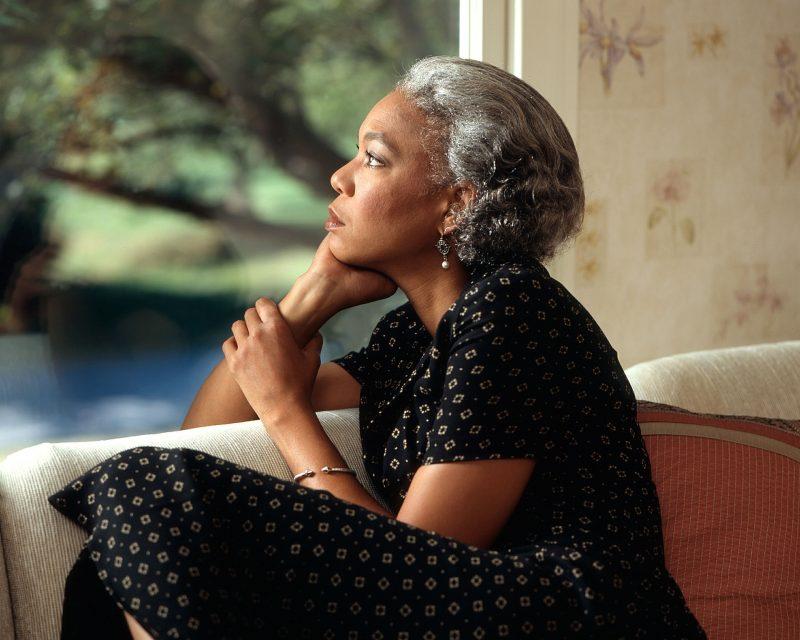 Mujer mirando por la ventana con expresión pensativa