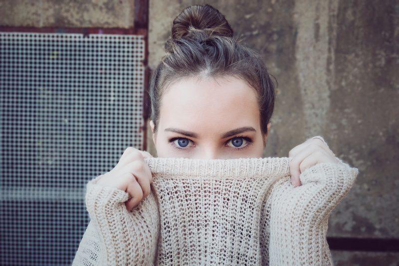 chica de ojos azules con el pelo recogido en un moño se tapa nariz y boca con un jersey.