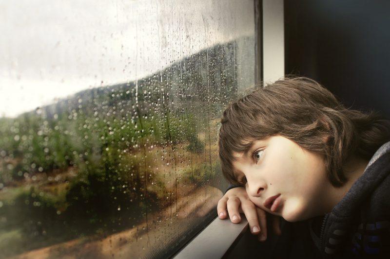 Niño con la cabeza recostada en la ventanilla de un tren, mirando paisaje con lluvia.