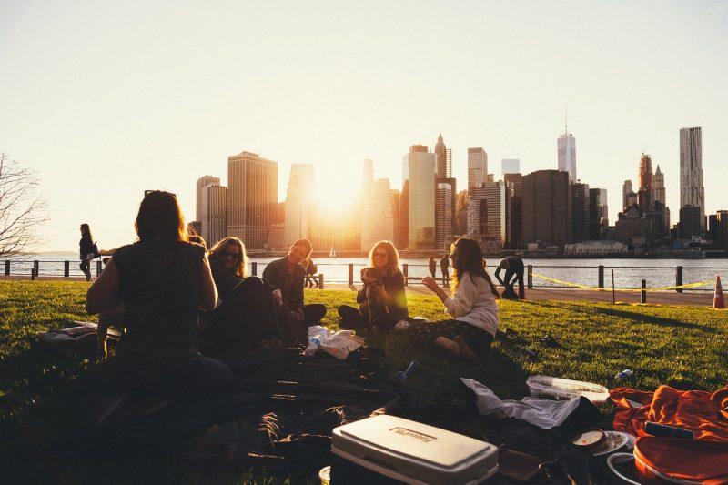 Grupo de adolescentes de picnic, en un parque junto a un río, con rascacielos en la otra orilla