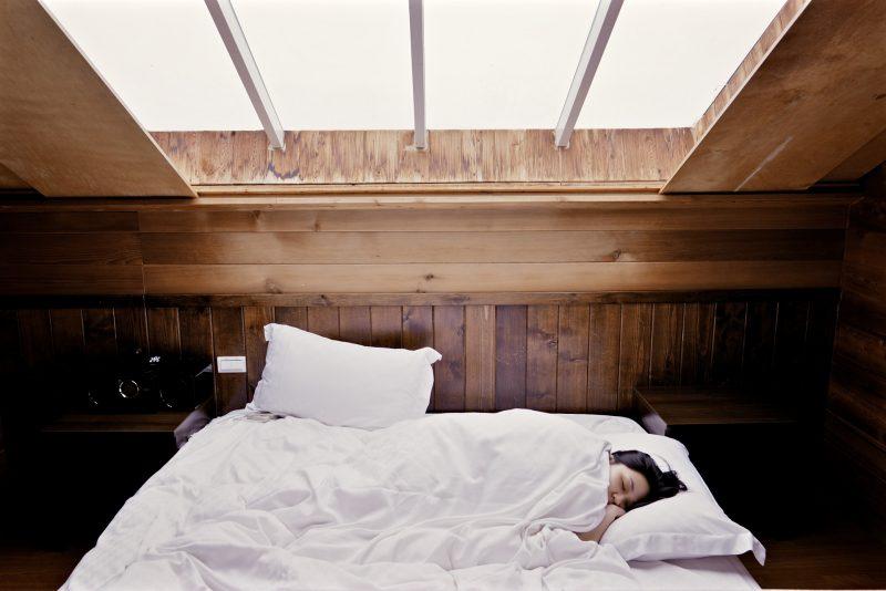 Persona durmiendo en una cama bajo un tragaluz