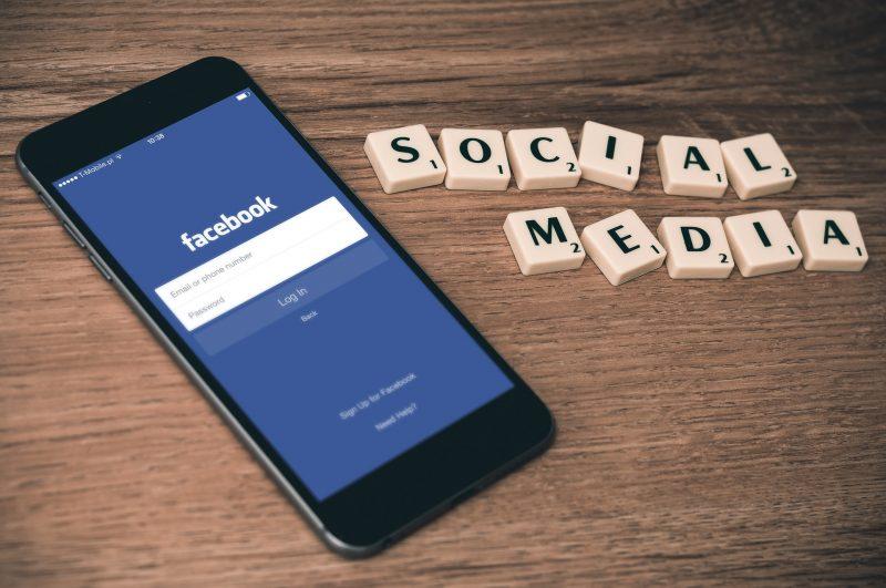 Teléfono mostrando la aplicación Facebook, y las palabras Social Media escritas con letras de Scrabble