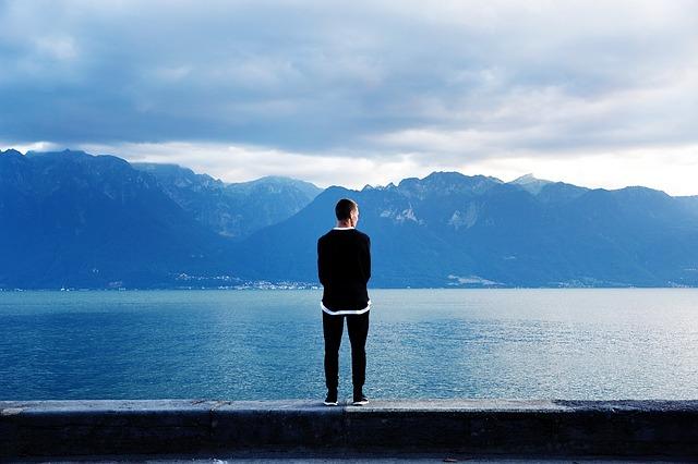 Chico mirando a una montaña y un lago, sobre un muro.