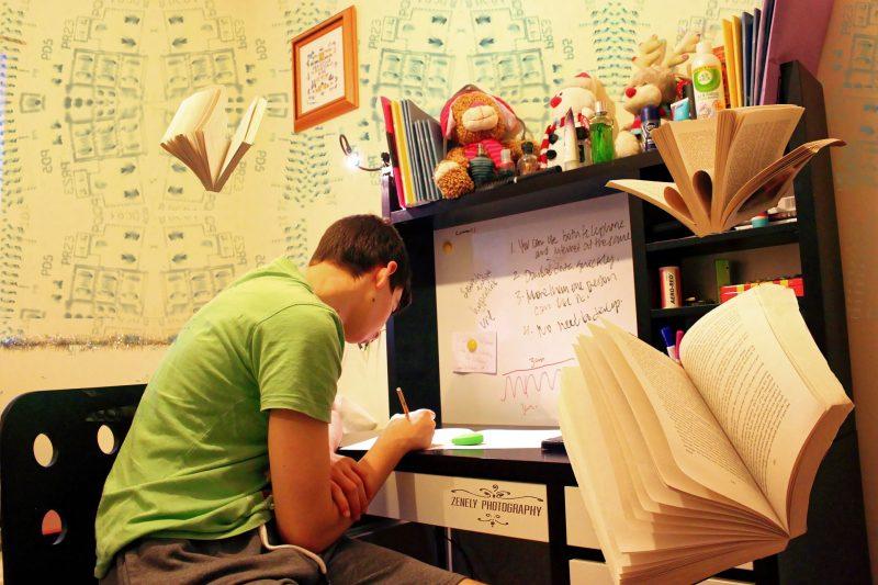 Adolescente escribe sobre una mesa de estudio, con dibujos y anotaciones sobre las paredes. Hay libros abiertos superpuestos en la imagen.