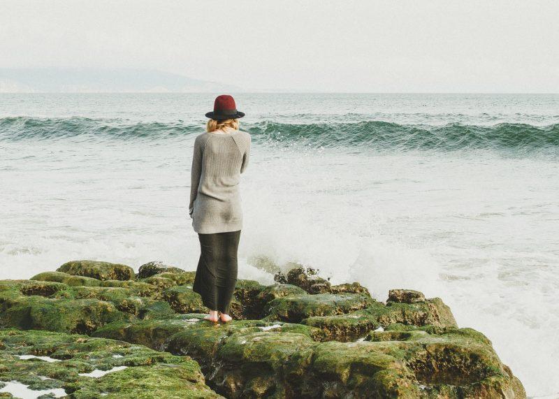 Mujer sobre rocas, mirando al mar