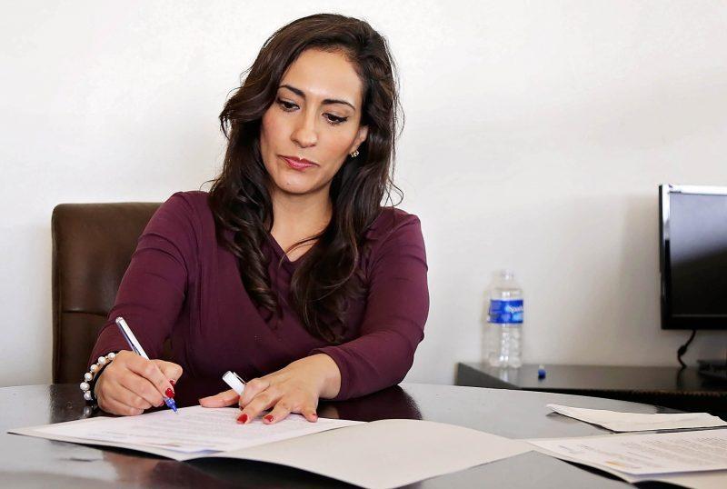 Profesional escribe en un dosier, sentada a una mesa.