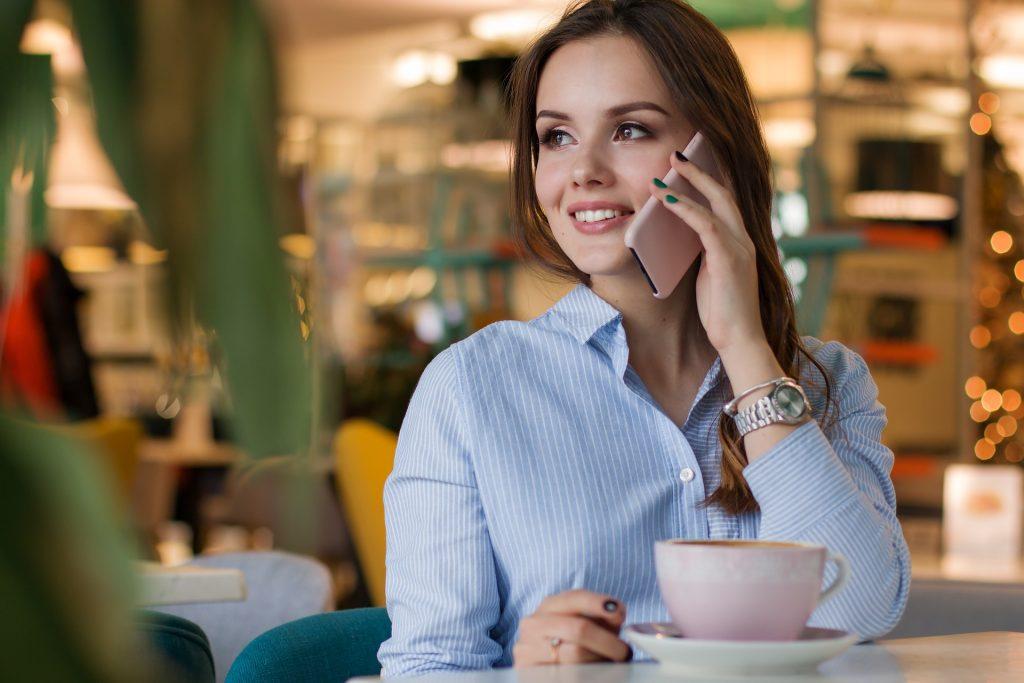 Una chica joven habla por teléfono sentada en una cafetería, con una taza de café delante