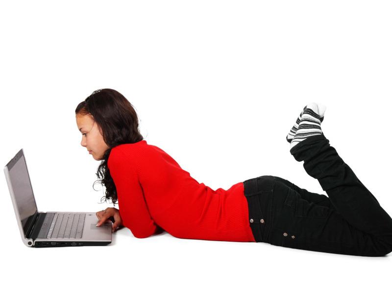 Chica tumbada mirando un ordenador portátil