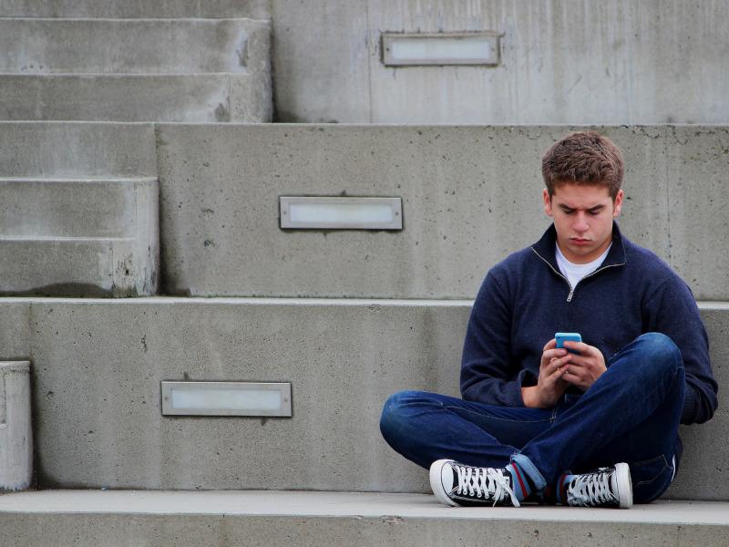 Adolescente juega con su teléfono móvil, sentado en unas escaleras