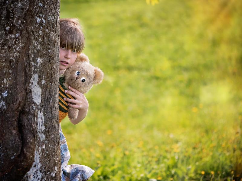 Niña con osito de peluche detrás de un árbol