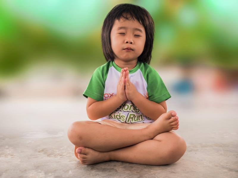 Niña meditando o haciendo yoga
