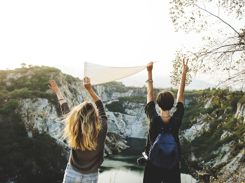 Dos jóvenes con los brazos levantados en una montaña