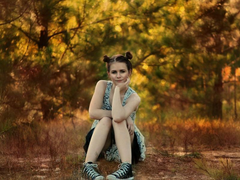 Adolescente con vestido y moños, sentada en el bosque