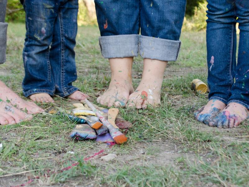 Pies y piernas de varios niños que juegan con pintura y brochas