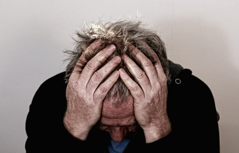 Un hombre adulto se mesa los cabellos con expresión preocupada.