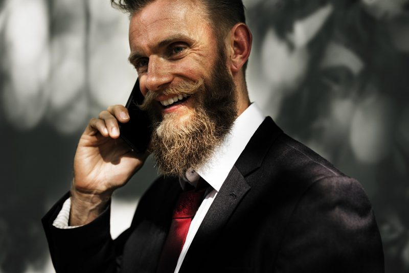 Señor de traje con bigote hablando por el móvil