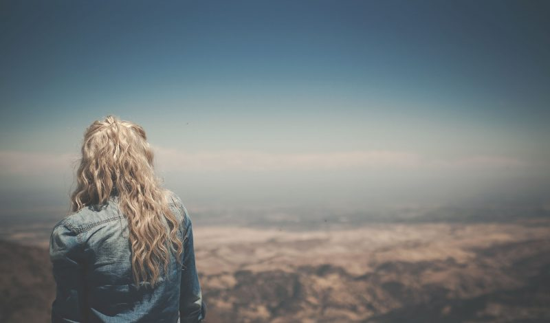 Joven contempla un paisaje desde las alturas.
