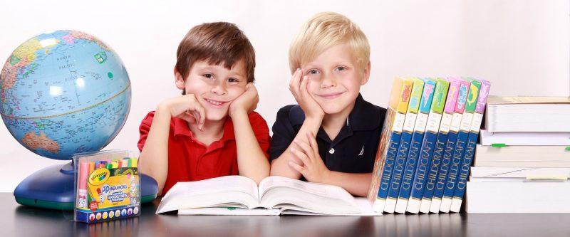 Dos niños con material escolar: enciclopedias, libros de estudio, globo terráqueo y rotuladores