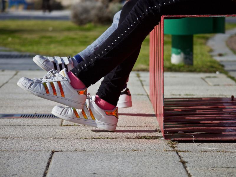 Piernas de dos adolescentes que están sentados en un banco con pantalones y deportivas