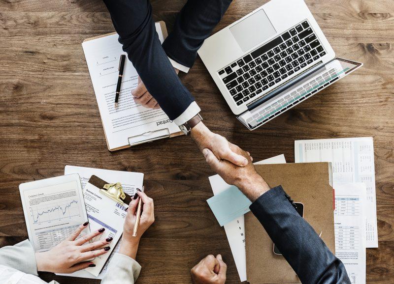 Reunión de negocios: dos miembros de un equipo se dan un apretón de manos como cierre de un contrato, mientras una tercera persona toma notas.