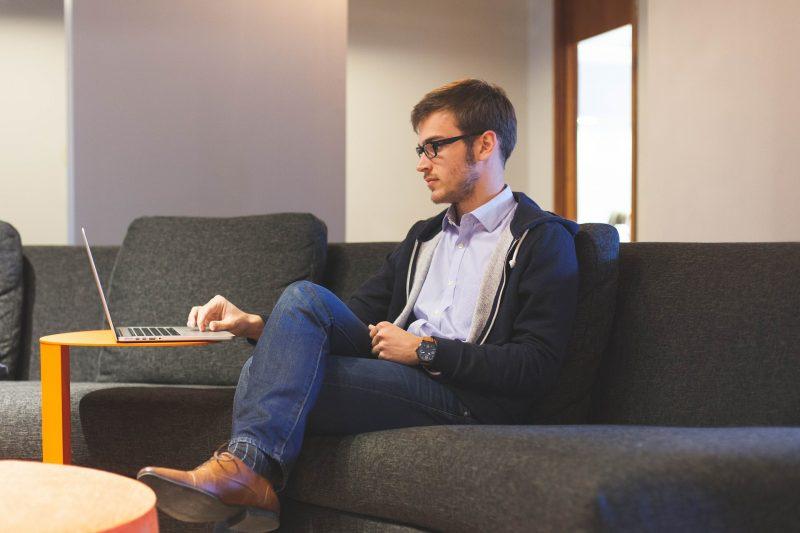 Joven sentado en un sofá gris, mirando su ordenador portátil