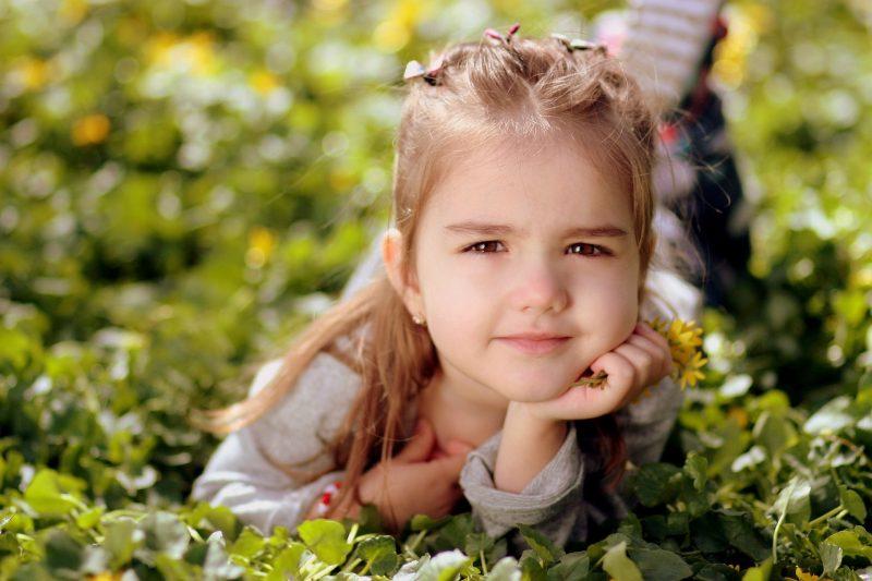 Niña tumbada sobre la hierba, con un ramillete de flores