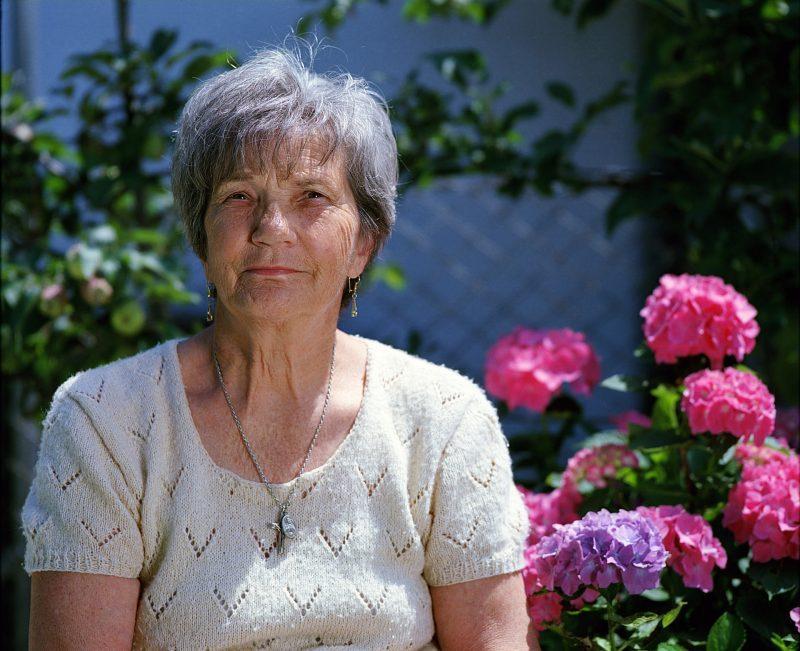 Señora mayor junto a hortensias