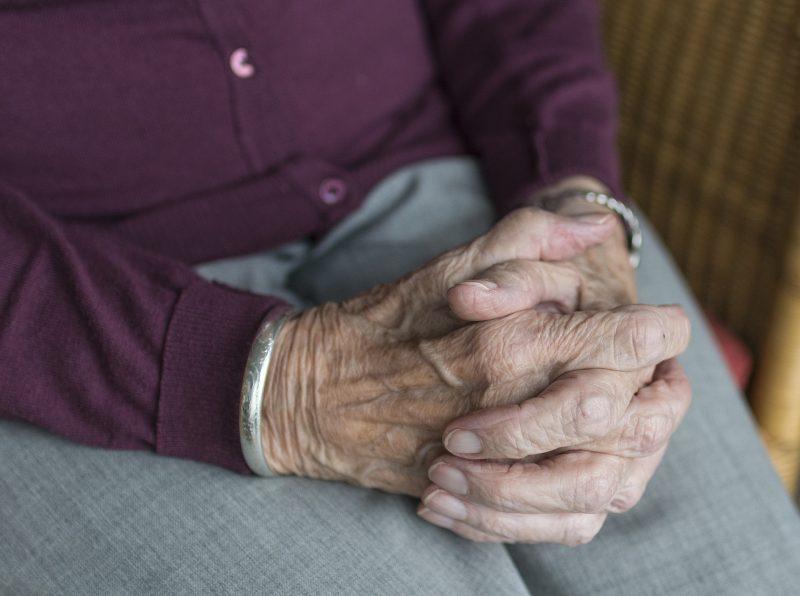Persona jubilada sentada, cruzando las manos