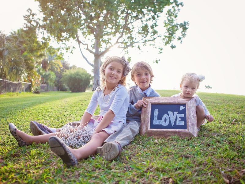 Tres niños sentados en la hierba sujetando un cartel con la palabra LOVE.