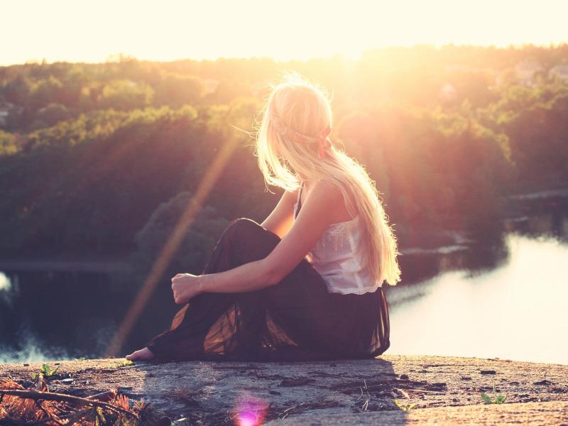 Adolescente sentada frente a un lago