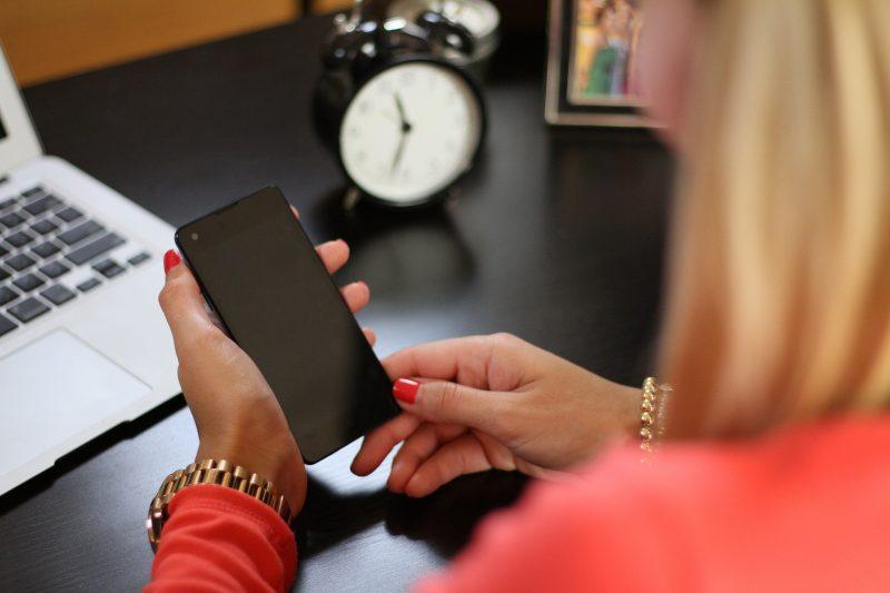 Una mujer mira su teléfono móvil