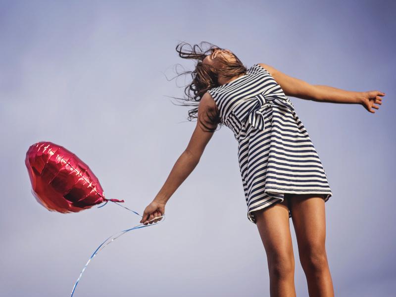 Chica joven saltando con globo en forma de corazón