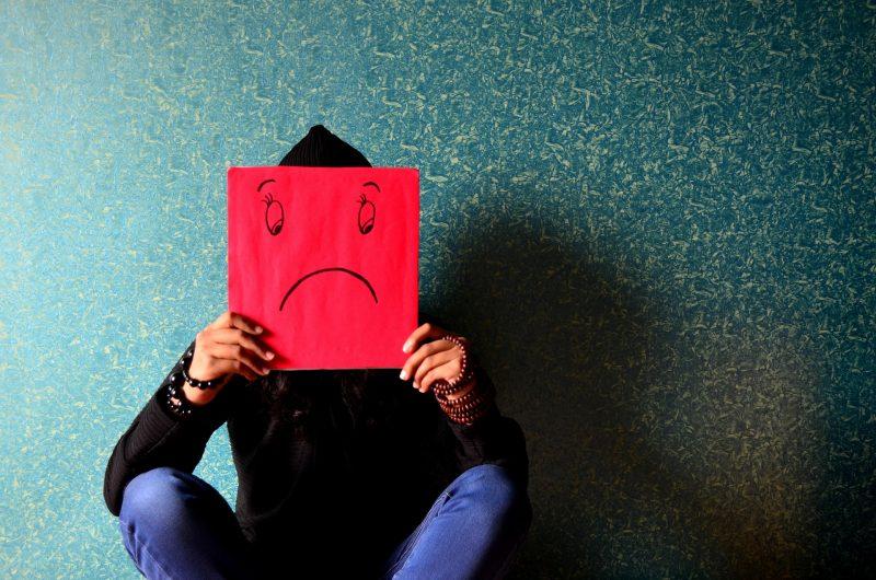 Una persona sujeta un emoticono triste frente a su cara.