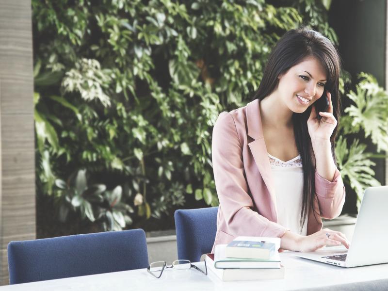 Mujer al teléfono con portátil