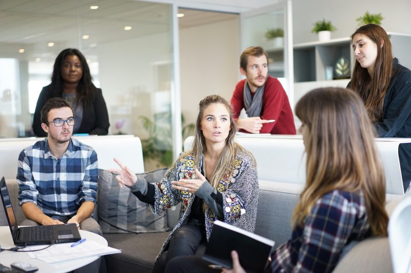 Reunión del equipo de trabajo, varias personas prestan atención a la chica que está hablando