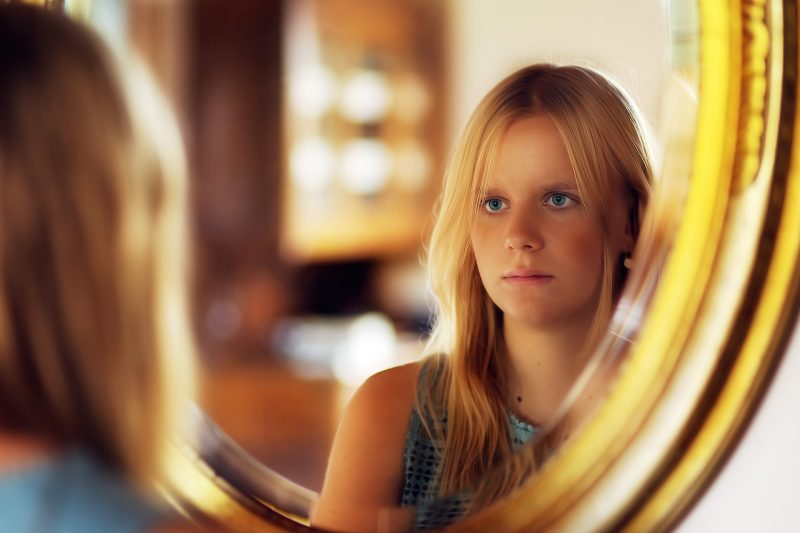 Una chica joven se mira al espejo.
