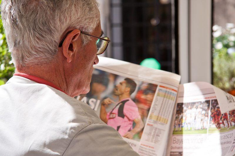 Una persona mayor leyendo un periódico de fútbol.