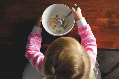 Aparece una niña pequeña comiendo cereales sola