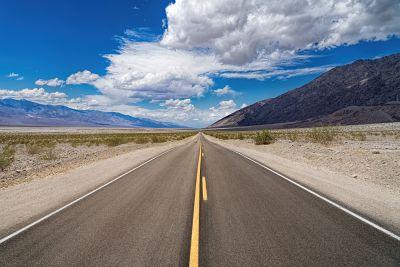 Carretera vacía con rayas amarillas en mitad del desierto.