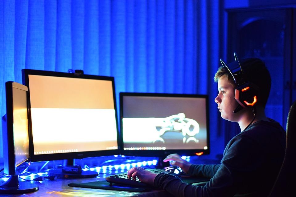 Adiccion a internet Bilbao. Chico jugando a juegos de ordenador, con varias pantallas de ordenador delante de él.