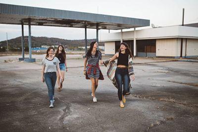 Cuatro chicas jóvenes o adolescentes caminan juntas por la carretera, sonrientes.
