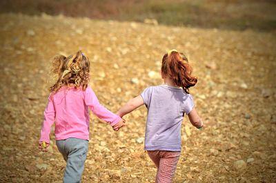 Dos niñas cogidas de la mano y corriendo por un terreno pedregoso.