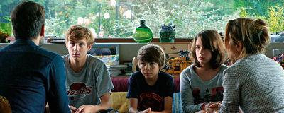 Padres hablando con sus tres hijos en casa