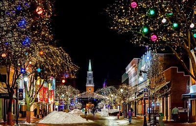 Escena navideña: ciudad con calles y árboles iluminados, nieve amontonada sobre la acera y personas paseando.
